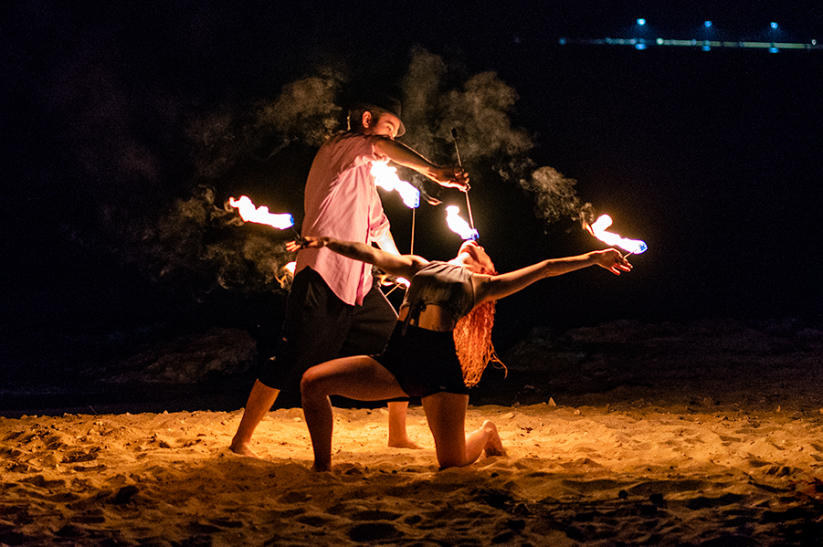 Person Feeding Fire to Kneeling Person on Beach