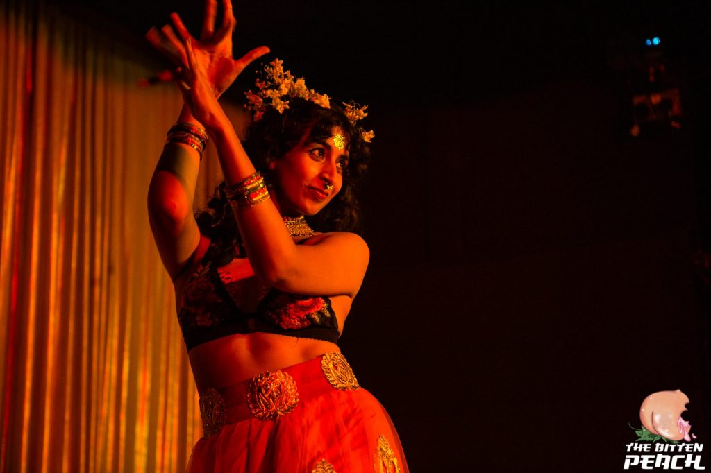 Jai wears a flower crown and performs Indian dance and burlesque on stage in orange lighting.