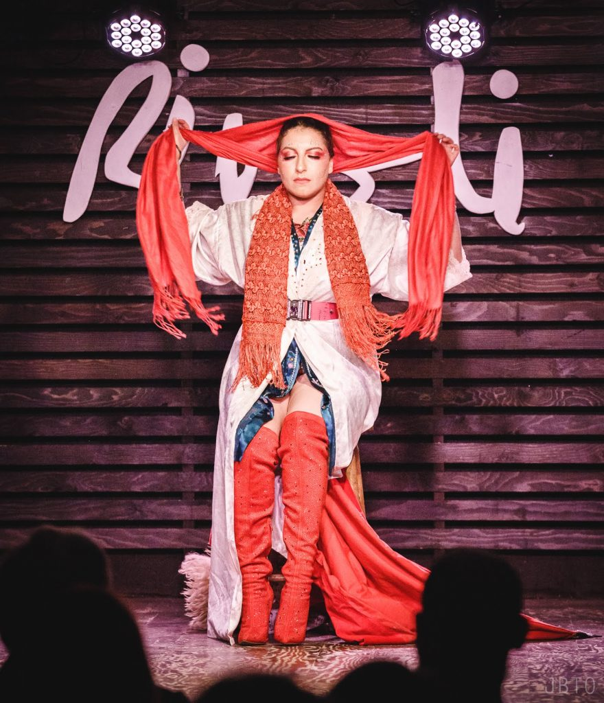 Fatima Noor El Deen Mahmoud pulls an orange silk scarf away from their face while sitting on stage during their burlesque performance.