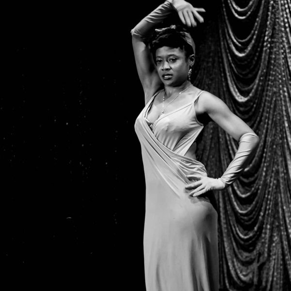 Ingride Denise performs on stage in a flowing evening gown with one arm over her head.