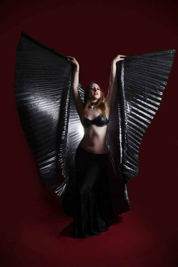 Burlesque performer and bellydancer Doe Demure poses in front of a dark red background flaring out black shiny isis wings on either side with her arms up and looking into the camera.