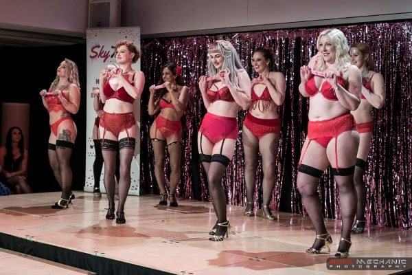 The burlesque dance troupe Chinas Locos Burlesque poses on stage wearing red lingerie and black stockings.