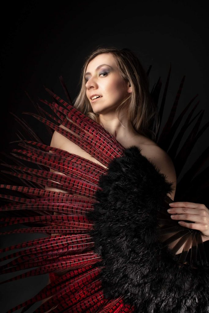 Burlesque and pole performer Carmen Dea Untamed poses behind a red and black delicate feather fan.
