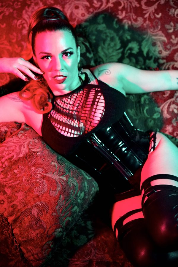 Burlesque performer Coco L'Amour poses under red and green lighting in a black corset and stockings with her hand lightly touching her face.
