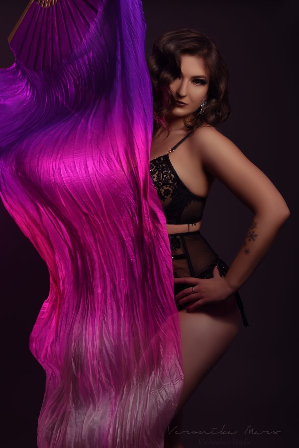 Burlesque performer Pandora Carnage poses in black lingerie with a purple and pink silk fan covering the right half of her body.
