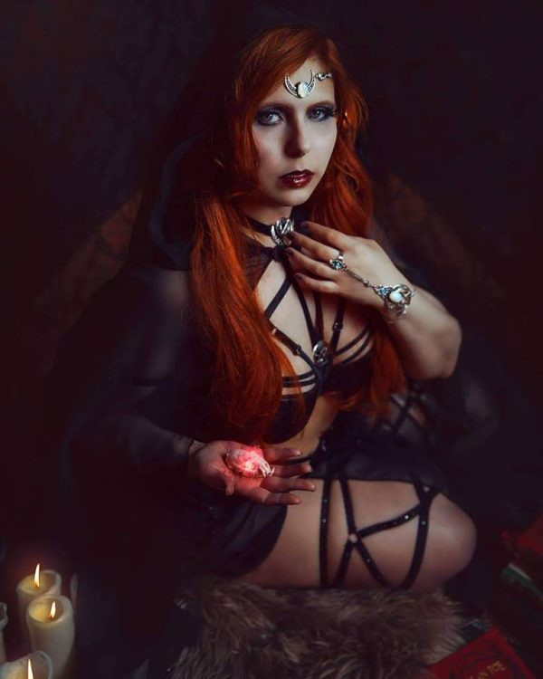 Burlesque and horrorlesque performer Devi Letalis poses in shadows wearing black scrappy lingerie and looking up towards the camera.