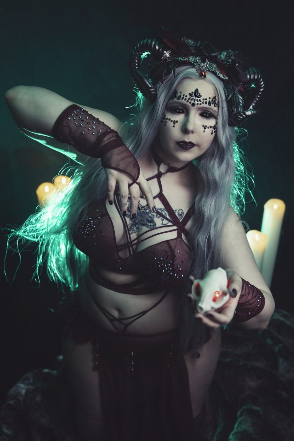 Burlesque and flow arts performer Devi Letalis poses in maroon lingerie, backlit by a green light, wearing a silver wig and black horns.