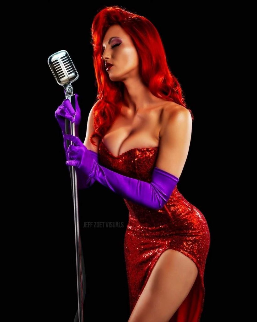 Burlesque performer and cosplay artist Ms. Margaret Jean poses with a silver microphone wearing a red wig, red sequin dress, and purple gloves, dressed up as the cartoon character Jessica Rabbit.