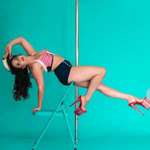 Pole dancer sparkling spitfire poses in a backbend sitting on a chair in front of a vertical pole wearing a sailor pin up costume.