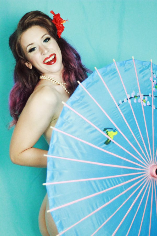 Burlesque dancer Cherry Valentine poses with a blue parasol covering her body as she smiles into the camera.