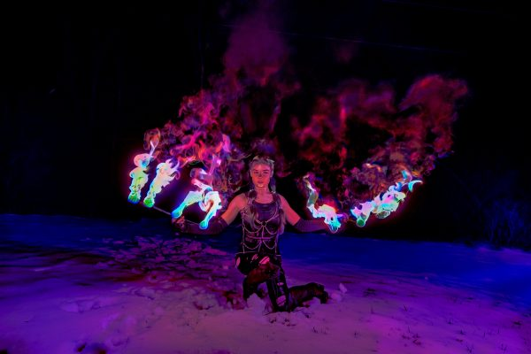 Fire dancer Maria Ekaterina kneels in the snow holding out flaming fans against a dark background.