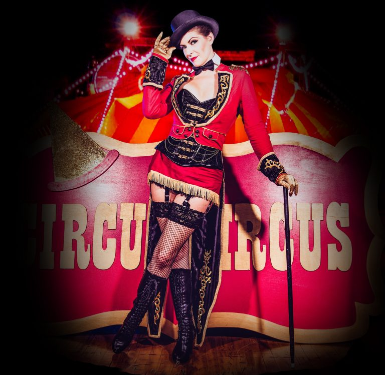 Burlesque performer Vixen DeVille is set against a red circus tent wearing a red and black ringmaster costume, posing with one leg crossed over the other and tipping her black top hat.