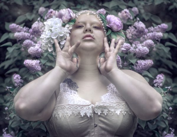 Burlesque performer Pixie Baroque poses in a beige lace op in front of purple flowers with her hands spread open under her jaw.