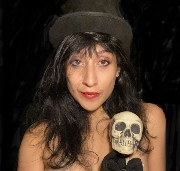 Pole dancer Queenciñera stands in front of the camera showing her bare shoulders, wearing a black hat and holding a skull.