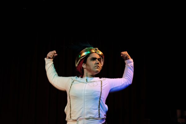 Drag King Rocoto Frenesí flexes their arms up in the air wearing a white button-down shirt and a gold hat.