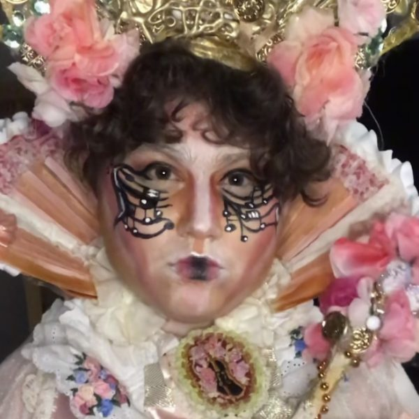 Drag performer Martin Vore poses wearing a floral crown and neck piece.
