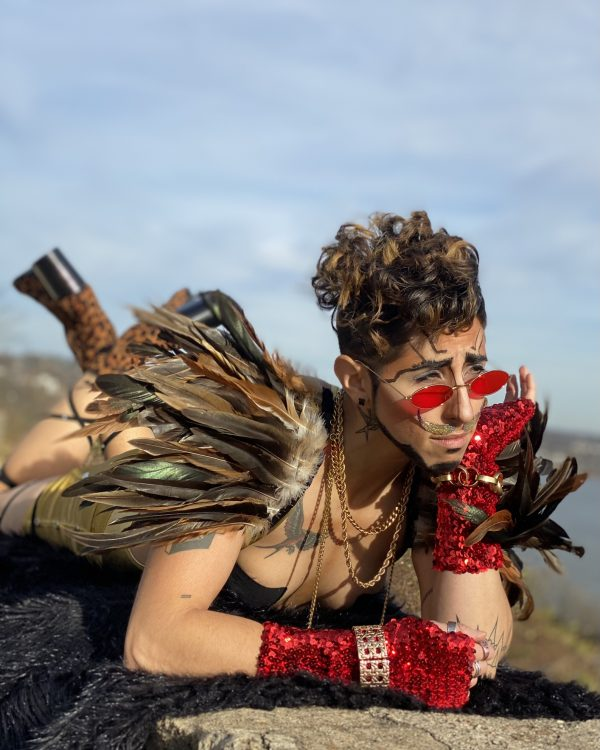 Drag King Prinze Valentino wears feathered shoulder pieces and red gloves and glasses and looks out to to the right side of the shot with their hand on their chin.