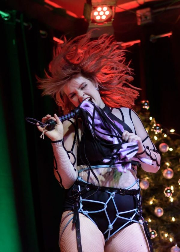 Circus and burlesque performer Emerald Fire flips her hair on stage holding a whip.