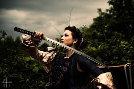 Burlesque performer Silver Kitsune holds a sword while looking up at a cloudy sky.