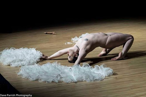 Burlesque performer Silver Kitsune performs a backbend on the floor holding out large while feather fans.